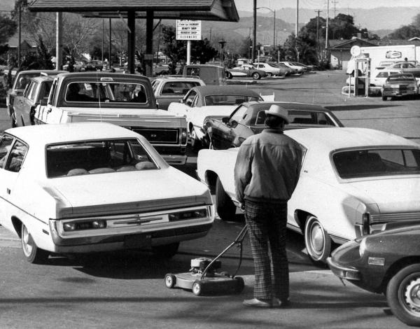 Drivers and a man pushing a lawnmower line up at gas station in San Jose, Calif., in March 1974.