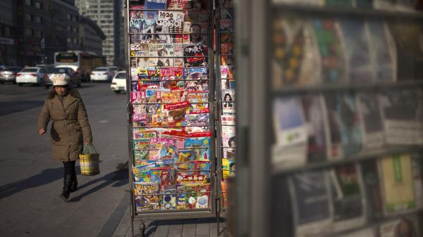 A woman walks past a newsstand in Beijing.