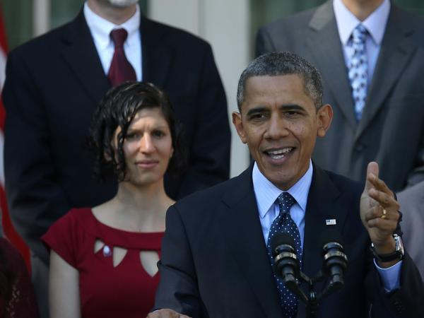 Karmel Allison, in red dress, stands behind President  Obama as he gives a speech Monday. Later, she almost fainted, briefly interrupting the address.