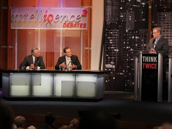 Richard Fisher (left) and Simon Johnson argue in favor of breaking up big banks in an <em>Intelligence Squared U.S.</em> debate, as moderator John Donvan looks on.