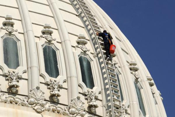 A renovation worker climbs atop the dome in 2010.