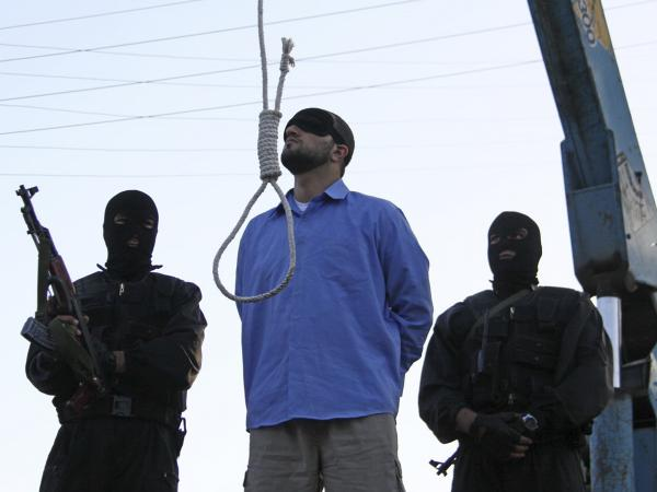 A blindfolded man convicted of armed robbery, kidnapping and the slaying of two policemen awaits execution in Tehran in 2011.