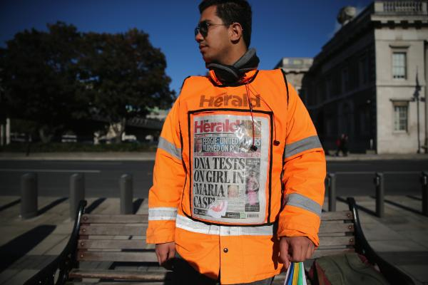A newspaper vendor wears a vest displaying front page of <em>The Herald</em> on Wednesday in Dublin. Irish authorities were waiting for DNA test results in relation to a girl removed by Gardai from a Roma family in Dublin, days after a similar case in Greece. The test showed the girl was the biological daughter of the Roma family.