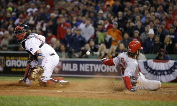 The Cardinals' Pete Kozma scores on a sacrifice fly as Red Sox catcher Jarrod Saltalamacchia can't handle the throw during the seventh inning of Game 2 of the World Series on Thursday. In an evolving St. Louis, the Cardinals remain a point of pride. (Matt Slocum/AP)