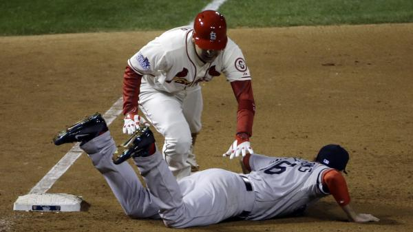The Cardinals' Allen Craig gets tangled with Red Sox's Will Middlebrooks in the ninth. Middlebrooks was called for obstruction and Craig went in to score the game-winning run.