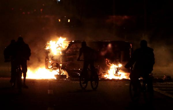 People ride bikes by a car on fire in a highway in Sao Paulo on Tuesday.