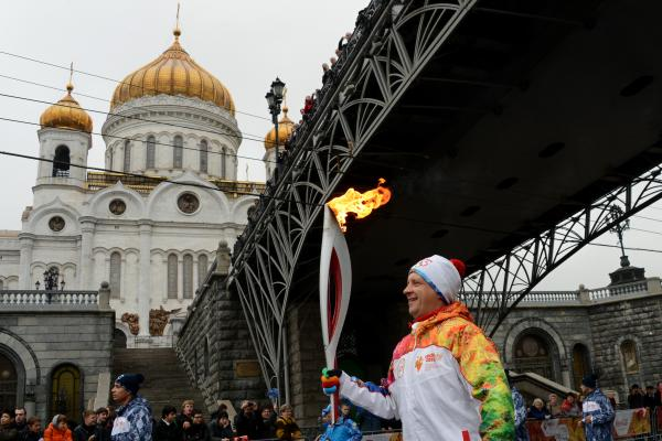 One of the participants of the Sochi 2014 Winter Olympic torch relay runs near the Christ the Savior Cathedral in Moscow, on Oct. 8. Controversies surrounding costs, security and gay rights swirl around the games, to be held in the Russian Black Sea resort city.