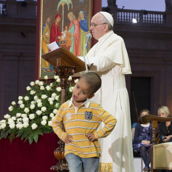 In this photo provided by the Vatican newspaper <em>L'Osservatore Romano</em>, Pope Francis reads his message as a young boy plays in front of him on the stage.