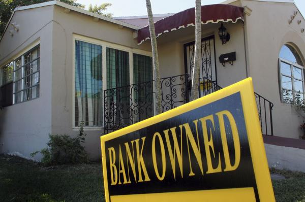 <p>A bank-owned sign is seen in front of a foreclosed home in Miami. Florida was among the hardest hit states in the real estate collapse.</p>