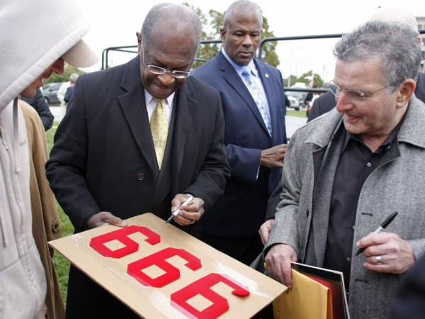 "<p>On the day he revised his tax plan to 9-0-9, Republican presidential candidate Herman Cain signs a supporter's ""999"" sign after unveiling his ""Opportunity Zone"" economic plan in front of the Michigan Central Station, an abandoned train depot in Detroit.</p>"
