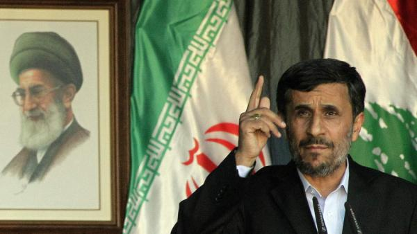A power struggle between Iranian President Mahmoud Ahmadinejad (right) and the country's supreme leader, Ayatollah Ali Khamenei (left, in portrait) is growing. There are signs that Khamenei may want to eliminate the presidency and replace it with the less powerful position of prime minister.