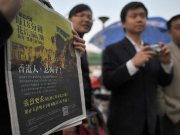 A girl holds a Hong Kong newspaper with an anti-mainland Chinese advertisement featuring a picture of a locust looking over the Hong Kong cityscape. The ad is one of the latest signs of Hong Kong fears that mainlanders are overrunning the territory.