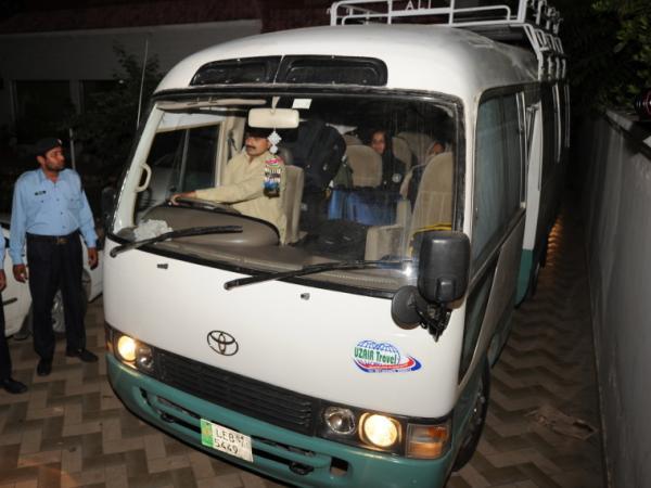 Pakistani policemen escort a minivan carrying family members of slain al-Qaeda chief Osama bin Laden, in Islamabad, earlier today.