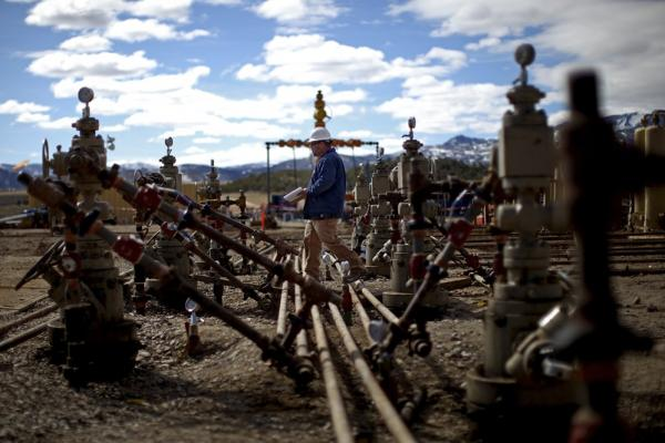 A worker walks across a series of gas pipes coming off wellheads at a natural gas drilling site near Rifle, Colo., run by Encana Oil and Gas.