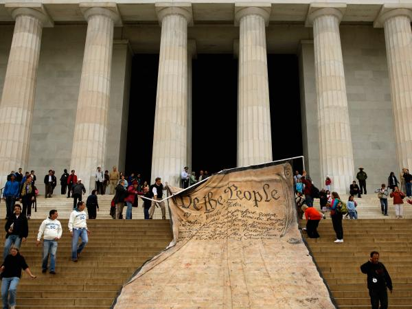 Volunteers unfurl a banner  with the Preamble to the Constitution during a demonstration against the Supreme Court's <em>Citizens United</em> ruling on campaign finance rules at the Lincoln Memorial in Washington, D.C., Oct. 20, 2010.