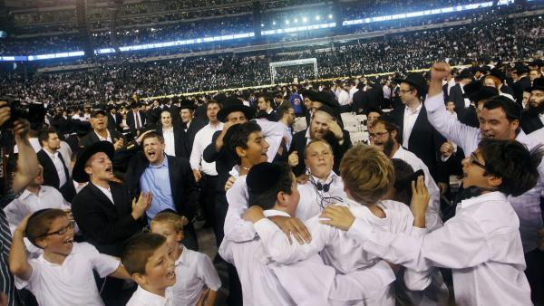 Orthodox Jews celebrate Siyum HaShas by dancing and singing at MetLife stadium in New Jersey on Wednesday.
