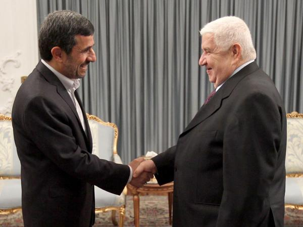 Iranian President Mahmoud Ahmadinejad (left) greets Syrian Foreign Minister Walid al-Muallem in the presidential palace in Tehran on July 29, in this official handout photo. The war in Syria threatens Iran's only ally in the Arab world.