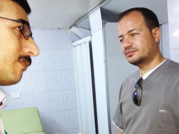 Dr. Zaher Sahloul (right) speaks with local staff at a field hospital in Aldana. Sahloul, a pulmonary specialist from Chicago, attended medical school with Syrian President Bashar Assad and is on his fifth medical mission to Syria.
