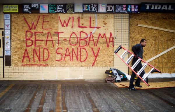 Raymond Souza carries away a ladder after boarding up a gift shop on the boardwalk in Rehoboth Beach, Del. President Obama and Gov. Romney have cancelled campaign events on Monday in anticipation of the superstorm.