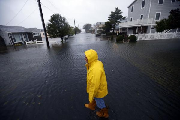 Al Daisey walks in the flood water in front of his home in Fenwick Island, Del.