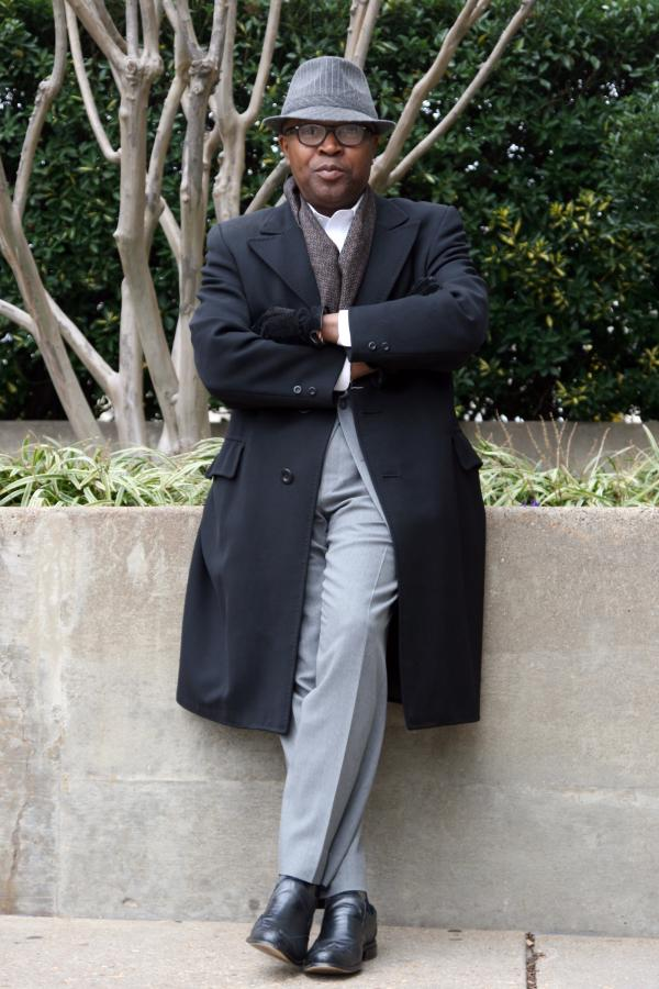 "Victor Holliday, associate producer of NPR's on-air fundraising, wears a light gray wool suit (DKNY Essentials) under a black vintage overcoat with fine English stitching (Regis Rex). He considers his style ""easy elegance."""
