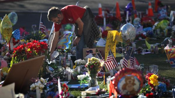 John Underhill waters flowers at a makeshift memorial for shooting victims outside the University Medical Center in Tucson, Ariz., on Jan. 20, 2011. Many of the plants and flowers at area memorials were replanted at a community garden.