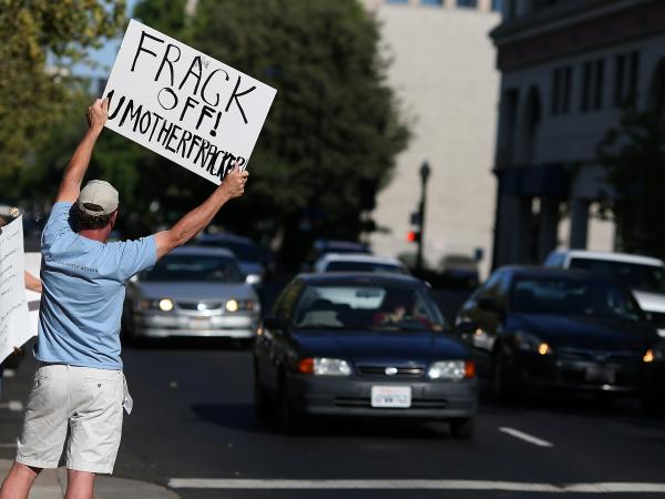 A protestor holds a sign against fracking during a demonstration outside of the California Environmental Protection Agency headquarters on July 25, 2012.