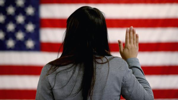 A woman takes the oath of allegiance during a naturalization ceremony at the district office of the U.S. Citizenship and Immigration Services in Newark, N.J.
