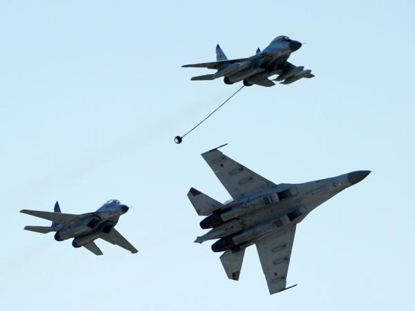 Russian MiG-29 (top), MiG-35 (left) and Su-35 (right) perform at an air show outside Moscow, in 2011.