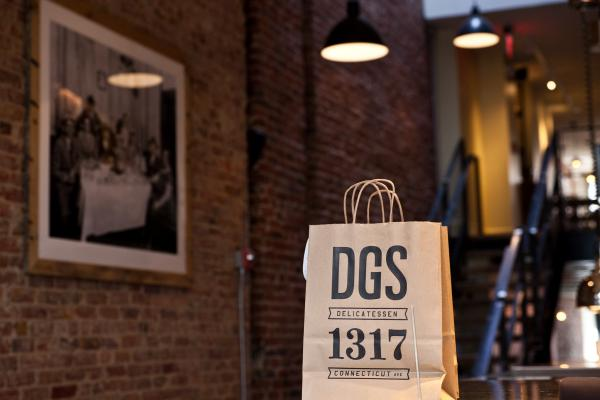 An earlier generation of deli owners, and relatives of the DGS partners, keeps watch over a to-go bag at the restaurant's walk-up counter.
