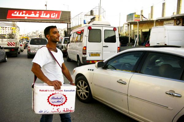 Ahmed Fahad sells ice cream from a Styrofoam cooler through tangled traffic at the Qalandia checkpoint between Jerusalem and the West Bank city of Ramallah.
