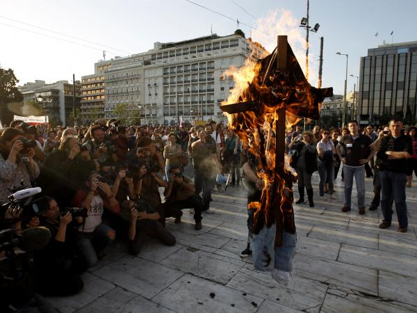 A protester burns an effigy depicting a Greek worker, in front of parliament in Athens on April 28. A few hundred public servants protested peacefully as lawmakers voted on a new austerity bill.