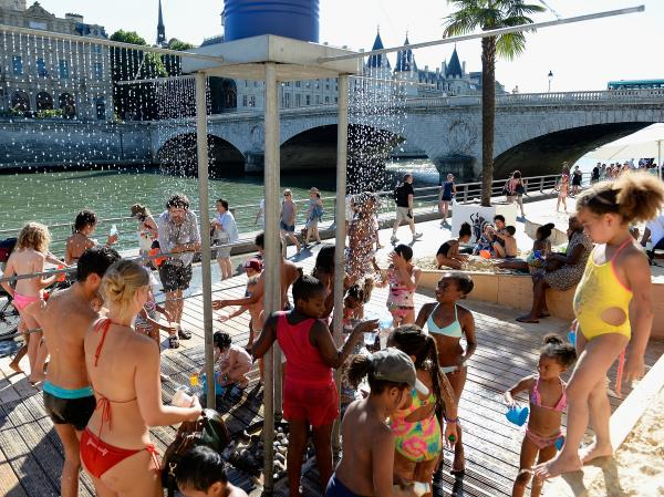 Tourists and Parisians alike cool down under jets of water at Paris Plage on the right bank of the Seine, on Aug. 1.