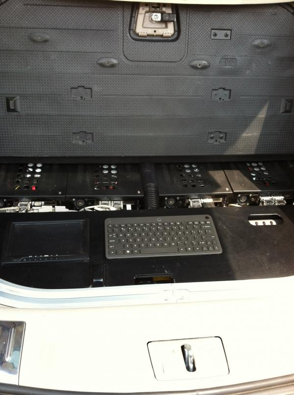 Four computers cooled by an air-conditioning system sit in the back of the car, below the floor where a spare tire would normally be.