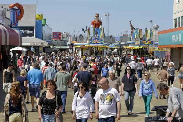 Large crowds of people walk along the newly rebuilt boardwalk on Memorial Day.