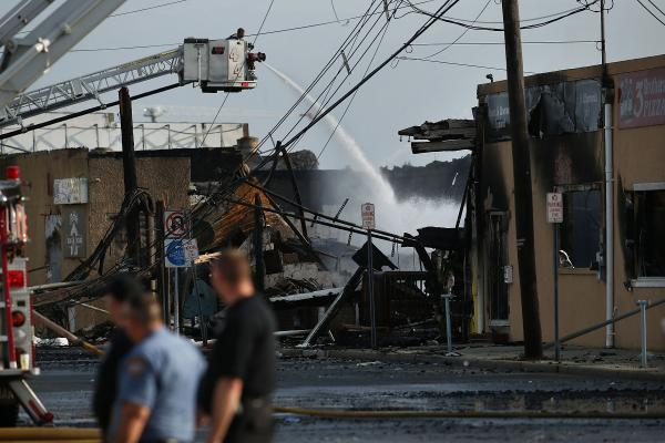 A firefighter sprays water on a hot spot at the scene of the fire Friday. Gov. Chirstie vowed that the state would rebuild.