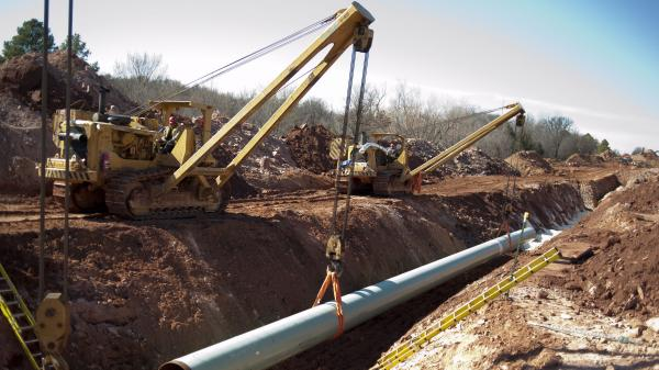 A 60-foot section of pipe is lowered into a trench during construction of the Gulf Coast Pipeline in Prague, Okla., in March. The Gulf Coast Pipeline, a 485-mile crude oil line, is part of the Keystone XL project and will run from Cushing, Okla. to Nederland, Texas. Although this southern stretch of the pipeline is nearly finished, the northern stretch is still under study.