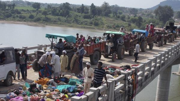 Indian villagers on tractors move past victims of a stampede on a bridge across the Sindh River in Madhya Pradesh state, India, on Sunday. Dozens of people died after a panic broke out.