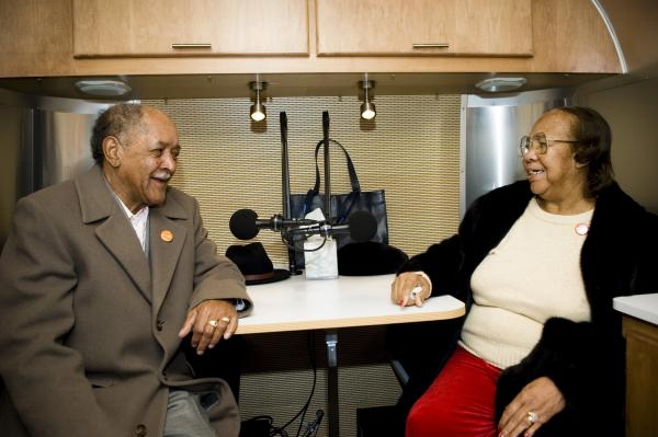 Two participants sit down inside a StoryCorps MobileBooth to record their story.