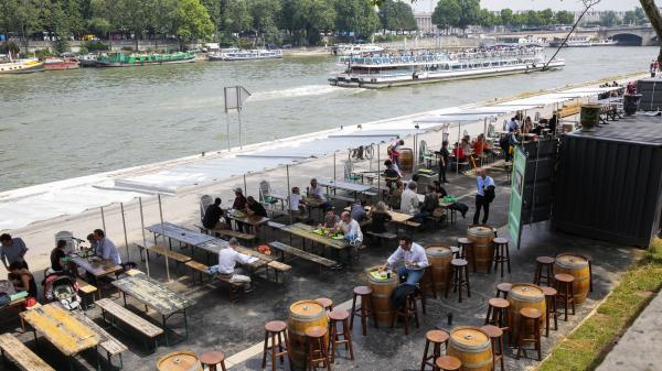 Parisians and tourists sit at a cafe along the Seine River. The mayor of Paris recently closed down a major highway along the river to open it up for pedestrians.
