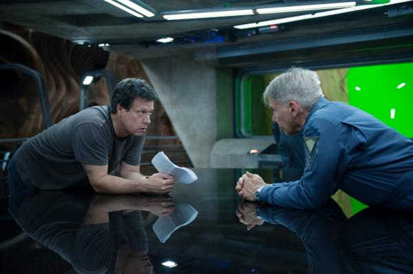 "Director and screenwriter Gavin Hood (left) talks with Harrison Ford, who plays Colonel Graff on the set of the new movie ""Ender's Game."" (Richard Foreman Jr., SMPSP, © 2013 Summit Entertainment, LLC. All Rights Reserved.)"