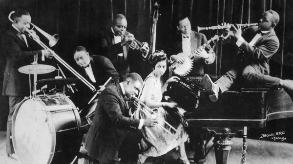 King Oliver's Creole Jazz Band in Chicago in 1923: Louis Armstrong is kneeling, from left to right behind him are Honore Dutrey, Baby Dodds, King Oliver, Lil Hardin, Bill Johnson and Johnny Dodds.