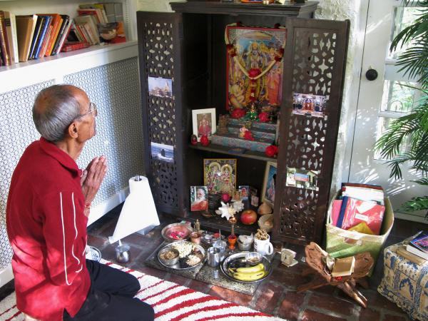 Ravindra Shukla, Aseem's father, kneels before the family altar as part of the holiday celebration.