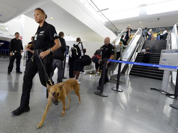 On patrol: A Los Angeles Police Department officer and her dog were among the security forces on duty over the weekend in Terminal 3 at Los Angeles International Airport. A gunman opened fire there Friday, killing a TSA officer and wounding several other people.