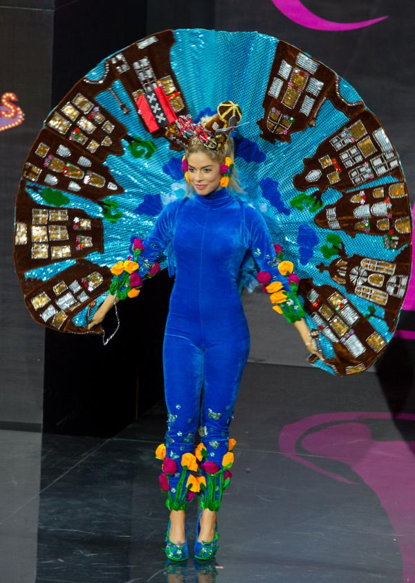 I just want you to pause and appreciate that she is wearing what appears to be a velvet jumpsuit with a standing Elvis cape made of buildings, a windmill <em>and</em> a bicycle on her head, and tulips on her pants. (Miss Netherlands: Stephanie Tency)