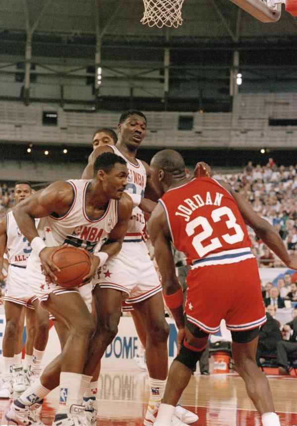 The West's Karl Malone (left) goes eyeball to eyeball with the East's Michael Jordan while Akeem Olajuwon looks down on the scene in the second half of the NBA All-Star Game on Feb. 2, 1989.