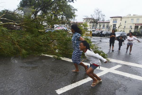 Residents rush to safety past a fallen tree as strong winds from Typhoon Haiyan hit Cebu City, Philippines, on Friday. The storm forced millions of people to flee to safer ground, damaging power lines and blowing apart houses.