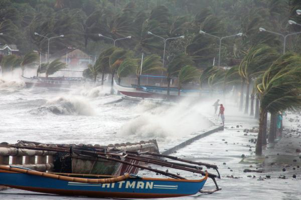 Legaspi City residents stand along a sea wall, as high waves and strong winds hit.
