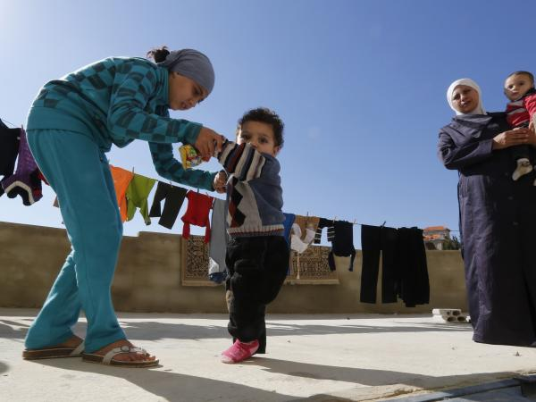 A Syrian refugee girl helps her brother walk as their mother watches at a mosque compound near Shebaa, Lebanon, on Oct. 28. The family suspects the boy has polio.