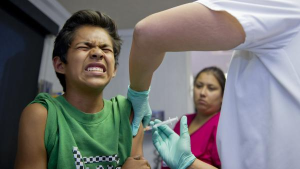 Public school student Julio Valenzuela, 11, grimaces as he gets a vaccination before the start of the school in Lynnwood, Calif., on Aug. 27. Vaccines are required for school attendance.